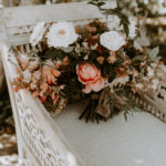A lush bridal bouquet rests on a wooden carved chair at this late summer boho wedding at Inn at Rancho Santa Fe.