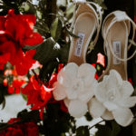 Jimmy Choo heels with a floral detail are styled next to bright bougainvillea.