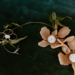 Beautiful Lele Sadoughi floral earrings and wedding rings are styled with greenery vine.