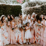 The bride poses with her bridesmaids in ruffled spaghetti strap gowns in peach and floral patterns. at this late summer wedding