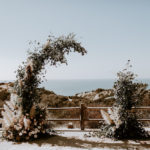 An asymmetrical ceremonial arch of eucalyptus, roses and pampas grass frames the Pacific Ocean at this late summer wedding at Torrey Pines Reserve in La Jolla, CA.
