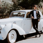 The groom poses with his white getaway car.