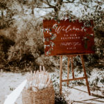 Wooden welcome sign with hand calligraphy rests next to a basket of white paper parasols at this late summer boho wedding at Torrey Pines Reserve.