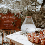 Wooden welcome sign with hand calligraphy at this late summer boho wedding at Torrey Pines Reserve.