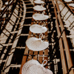 Guests keep cool in the late summer sun with wicker hand fans placed on their ceremony chairs.