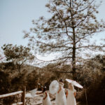 Flower girls in boho white dresses lead the way to the ceremony holding paper parasols.
