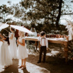 The flower girls and ring bearer wait for guests to arrive while calling off under paper parasols.
