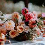 Colorful floral centerpieces of peach, fuchsia and amber decorate the tables at this late summer boho wedding at Inn at Rancho Santa Fe.
