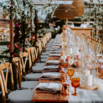 Feasting tables decorated with colorful floral, fruit, candles, copper mugs and amber goblets are set under a canopy of draped fabric, vines and boho wicker lanterns at this late summer wedding at Inn at Rancho Santa Fe.