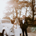 A bride and groom laugh and pose in front of their vintage white getaway car post-ceremony.