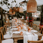 Feasting tables decorated with colorful centerpieces of floral, fruit and candles and copper mugs set under a canopy of draped fabric and boho wicker lanterns at this late summer wedding at Inn at Rancho Santa Fe.