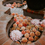Colorful Peach and Pink dahlias float in a moroccan -style fountain at this late summer boho wedding.