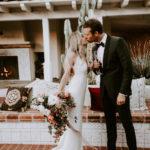 A boho bride and groom toast and kiss at their late summer wedding at Inn at Rancho Santa Fe.
