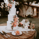 A beautiful 4 tiered white wedding cake with fresh floral decor sits on a boho wooden table with etched toasting flutes at this late summer wedding at Inn at Rancho Santa Fe.