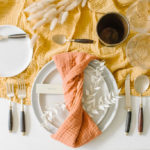 A textured napkin is twisted around the plates and dresses up a simple Fall-Inspired tablescape.