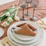 A textured napkin is folded like a fortune cookie and dresses up a modern tablescape.