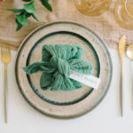 A textured napkin wraps a favor in the Furoshiki style at this simple place setting.