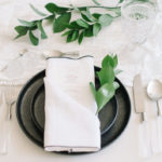 A white linen napkin with black contrasting edge is folded to house an elegant menu and dresses up a simple, textured tablescape.