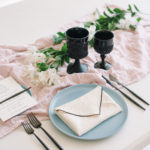 A white linen napkin with black contrasting edge is folded like an envelope and dresses up a simple, textured tablescape.