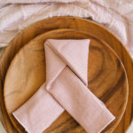 A pink linen napkin with white contrasting edge is folded into a geometric knot and rests top an acacia wooden plate setting.
