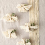 Mini wedding favor bundles wrapped in the furoshiki method are decorated with sprigs of rosemary.