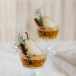A seasonal winter specialty cocktail with pear, cinnamon and rosemary garnish.