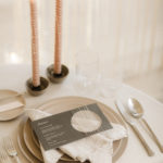 A modern minimalistic tabletop place setting includes textured helix taper candles.