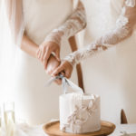 Two brides cut their mini vegan wedding cake together.
