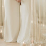 Two brides embrace surrounded by soft candles and romantic fringe curtains at their micro wedding ceremony.