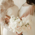 Two brides embrace with their bouquets at their elopement ceremony.