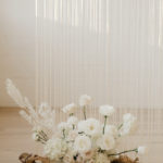 A floor arrangement of soft textured blooms and driftwood adds romance to the ceremony location.