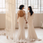 Two brides are surrounded by candles and romantic fringe as they begin their first dance.