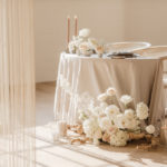A romantic table for two is set with a neutral color palette, soft floral and geometric arc shaped furniture.