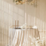 The table for two is surrounded by flowing fringe, soft candles and neutral floral.