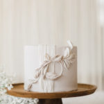A mini cake is decorated with soft geometric shapes and fringe to mimic the wedding design aesthetic.