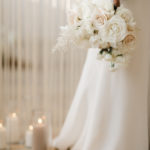 A soft bouquet of textured neutral florals is held at the bride's side.
