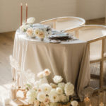 A romantic table for two in a half circle is decorated with soft candle light and neutral textured floral.