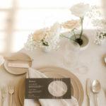 A simple neutral modern place setting includes a geometric cutout menu and romantic ikebana floral arrangements.