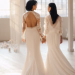 Two brides hold hands as they walk towards their first dance.